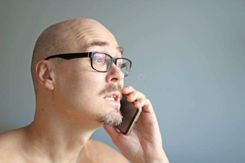 Młody przystojny mężczyzna w czarnych szkłach opowiada na telefonie Duzi problemy, skandal, zła wiadomość zbliżenie odizolowywają zdjęcie royalty free