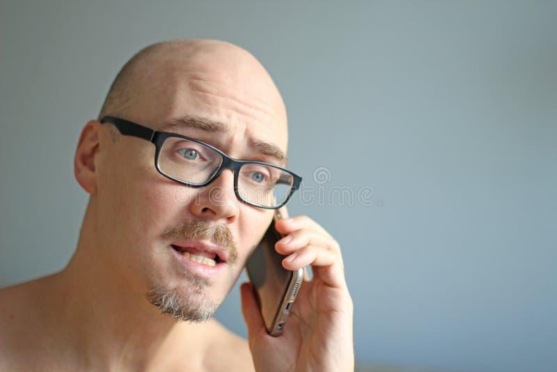 Młody przystojny mężczyzna w czarnych szkłach opowiada na telefonie Duzi problemy, skandal, zła wiadomość zbliżenie odizolowywają zdjęcia royalty free