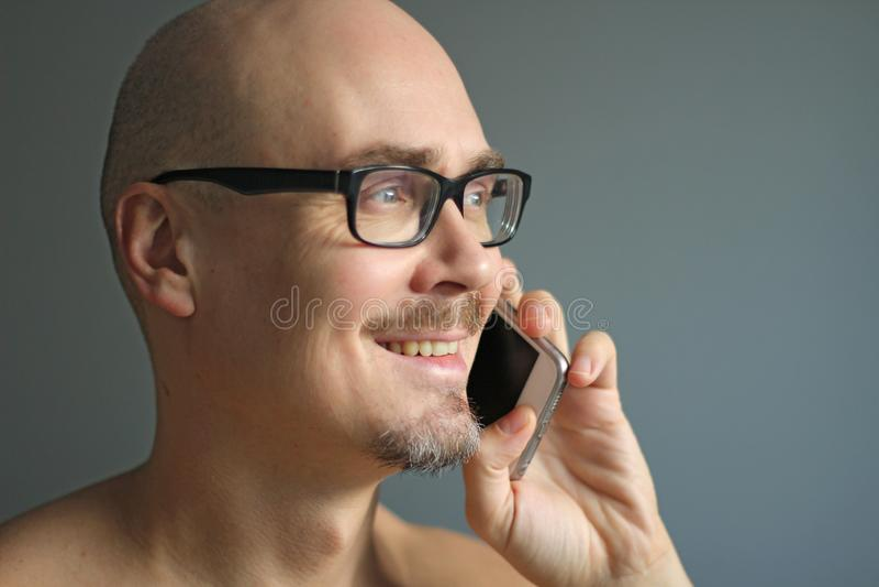 Młody przystojny mężczyzna w czarnych szkłach opowiada na telefonie, ono uśmiecha się zbliżenie odizolowywający mężczyzna portret obraz stock
