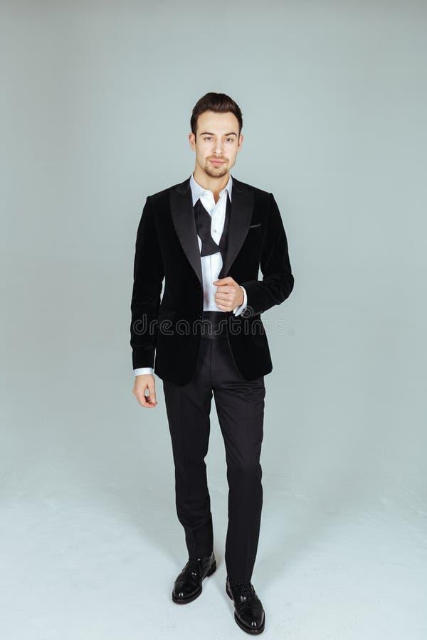 Młody przystojny mężczyzna w kostiumu, pozyci i patrzeć kamerę, fotografia royalty free