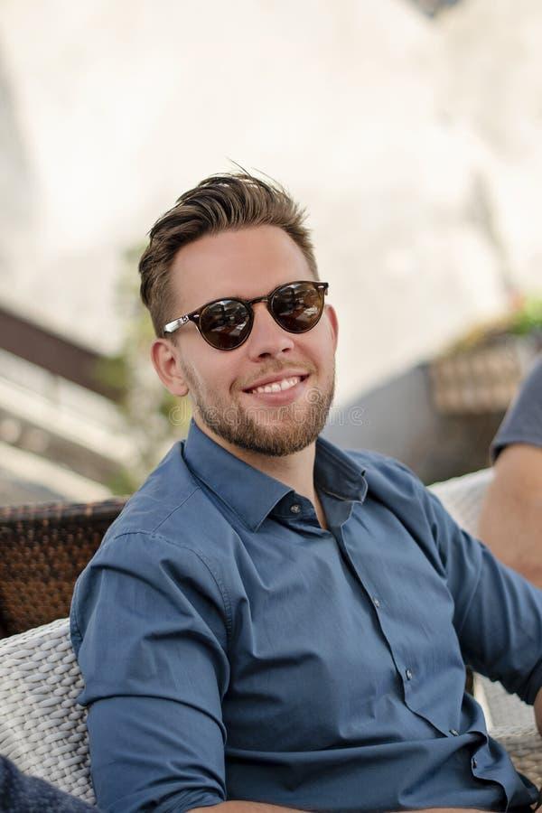 Młody przystojny mężczyzna w okularów przeciwsłonecznych ono uśmiecha się obrazy stock