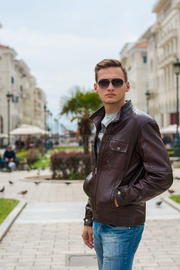 Młody przystojny mężczyzna w okularach przeciwsłonecznych, turysta, na zwyczajnej Aristotle ulicie w centrum Saloniki, Grecja obraz stock