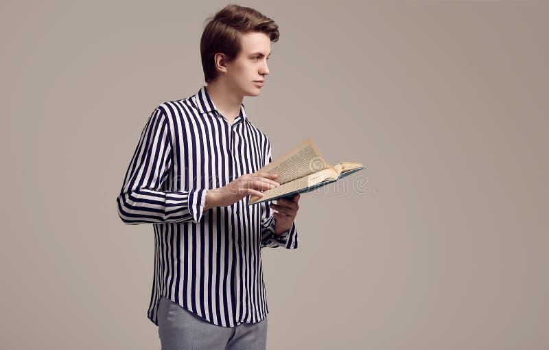 Młody przystojny mężczyzna w pasiastym koszulowym czytaniu książka na szarym tle obrazy stock