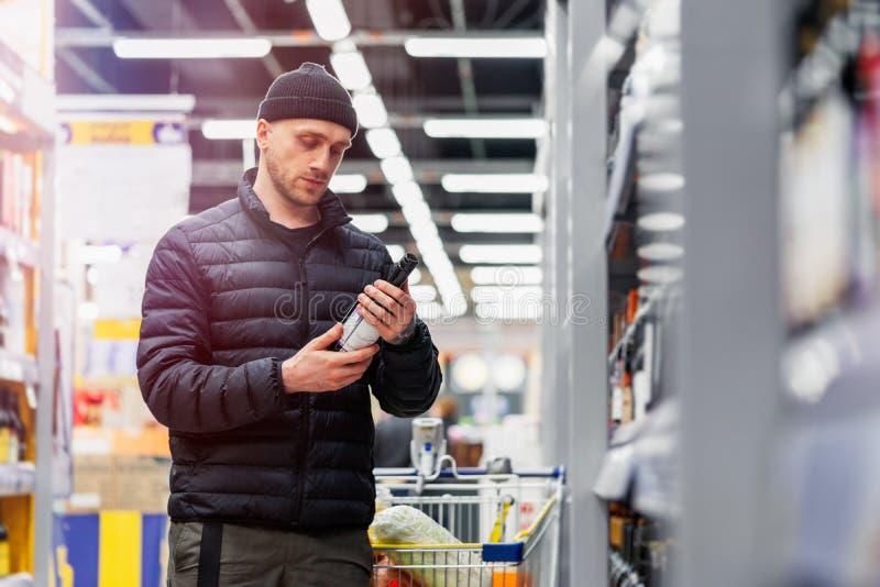 Młody przystojny mężczyzna wybiera wino w supermarkecie Sprawa wino wybór fotografia stock