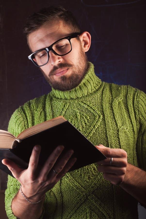 Młody przystojny mężczyzna z brodą w zieleni dział pulower czytelniczą książkę obraz stock