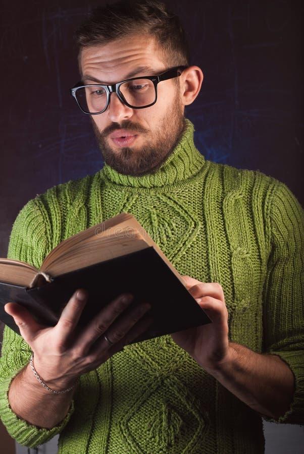 Młody przystojny mężczyzna z brodą w zieleni dział pulower czytelniczą książkę fotografia stock