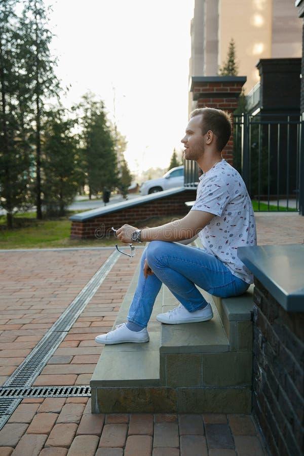 Młody przystojny mężczyzna z jeży się siedzi na granitowym schody blisko ceglanego domu na lato wieczór obrazy stock