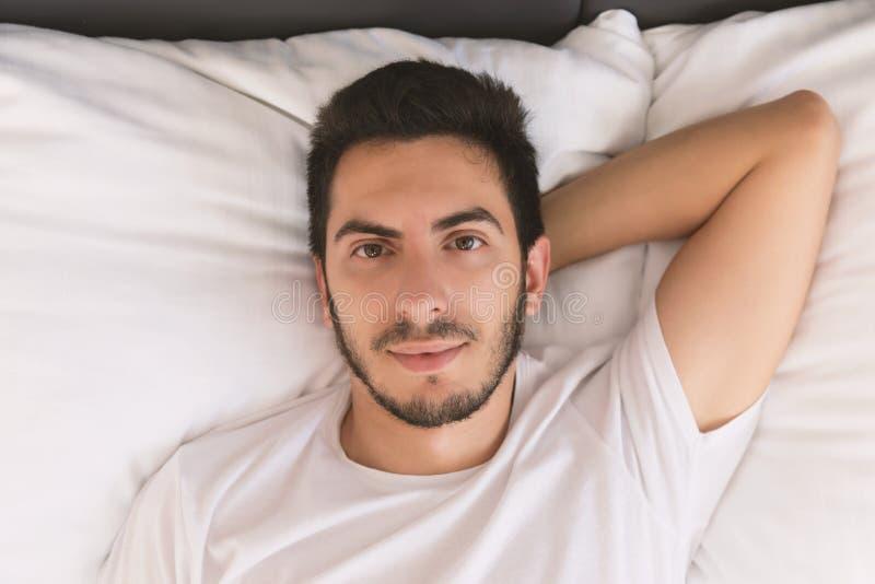 Młody przystojny mężczyzny dosypianie w jego łóżku obraz stock