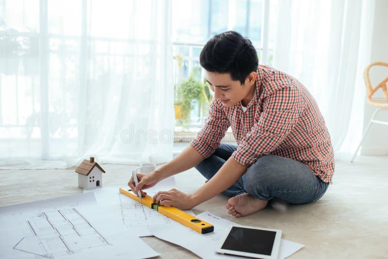 Młody przystojny męski azjatykci architekt pracuje w domu na podłoga fotografia stock