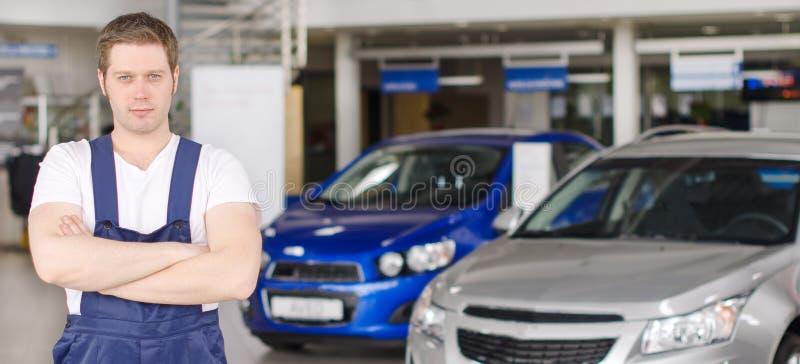 Młody przystojny mechanik w przedstawicielstwie firmy samochodowej obraz stock