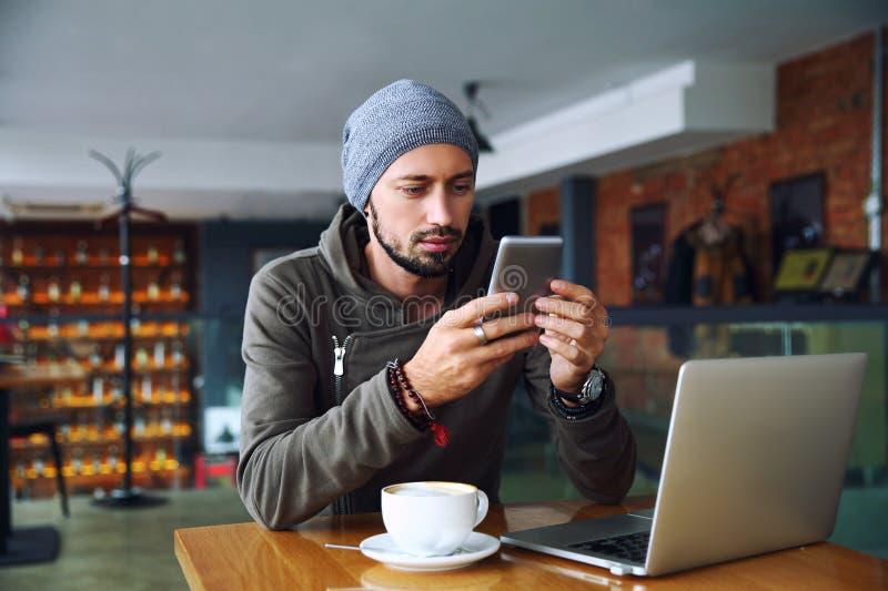 Młody przystojny modnisia facet przy restauracją używać telefon komórkowego zdjęcie stock