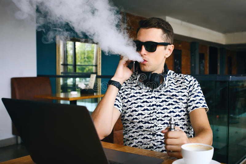 Młody przystojny modnisia mężczyzna insunglasse obsiadanie w kawiarni z filiżanką kawy, vaping i uwolnieniami, chmura opary zdjęcie royalty free