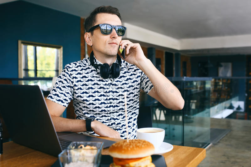 Młody przystojny modnisia mężczyzna siedzi w cukiernianym opowiada telefonie komórkowym w sunglases Laptop, filiżanka kawy i chee obrazy stock