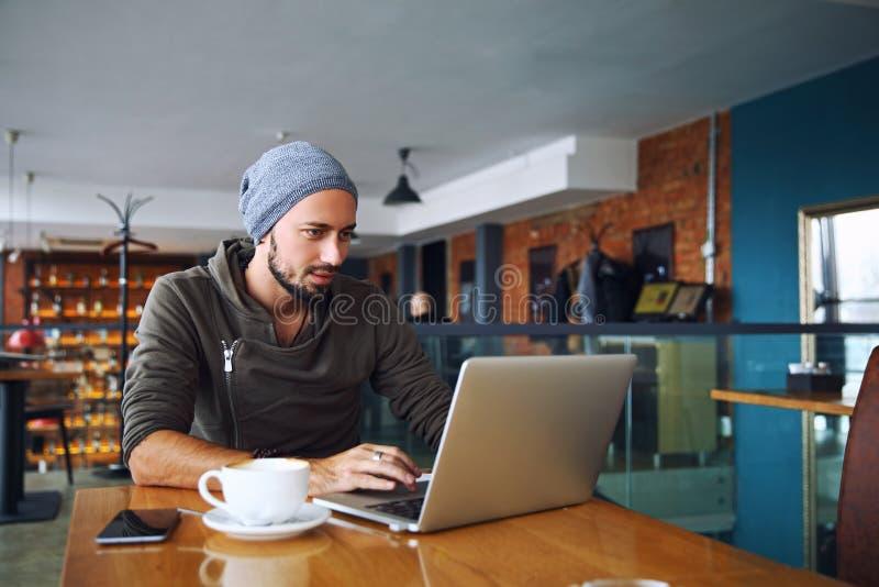 Młody przystojny modnisia mężczyzna z brodą używa laptop w bufecie obraz royalty free