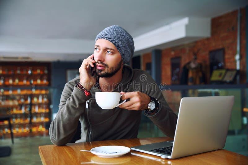 Młody przystojny modnisia mężczyzna z brody obsiadaniem w cukiernianym opowiada telefonie komórkowym, trzyma filiżankę kawy Lapto obraz royalty free