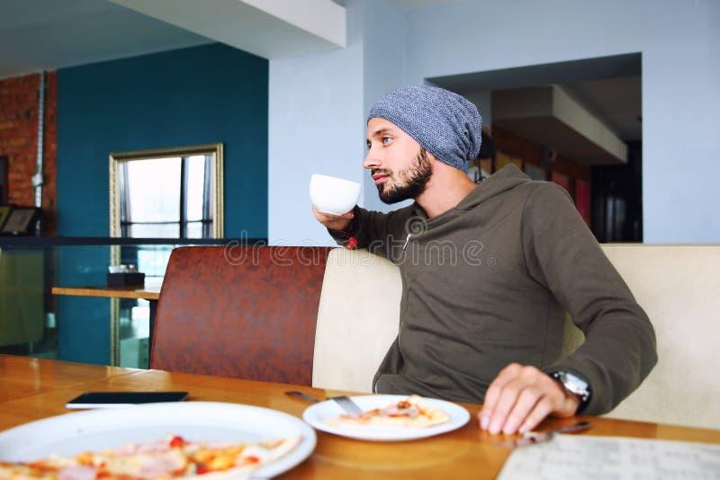 Młody przystojny modnisia mężczyzna z brody obsiadaniem w cukiernianym opowiada telefonie komórkowym, trzyma filiżankę kawy Lapto zdjęcia royalty free