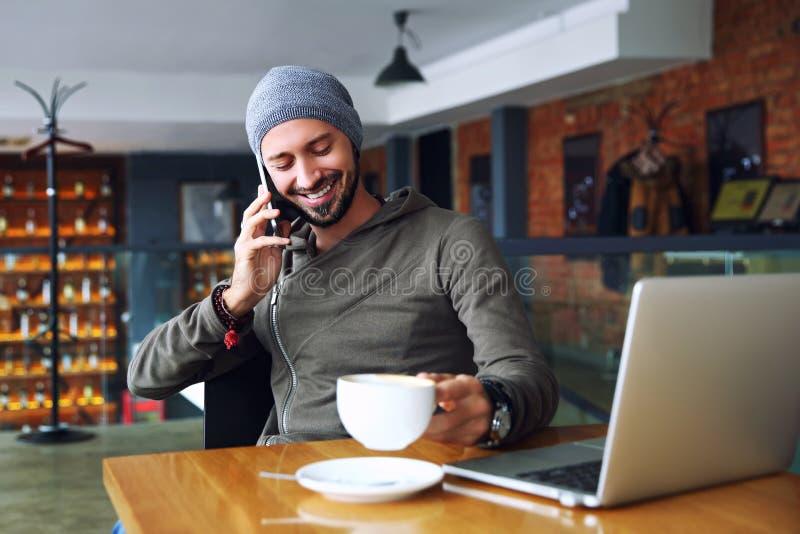 Młody przystojny modnisia mężczyzna z brody obsiadaniem w cukiernianym opowiada telefonie komórkowym, trzymający filiżankę kawy i zdjęcia stock
