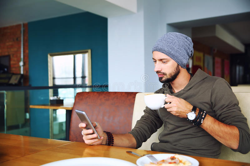 Młody przystojny modnisia mężczyzna z brody obsiadaniem w kawiarni używać telefon komórkowego, trzyma filiżankę kawy obrazy royalty free