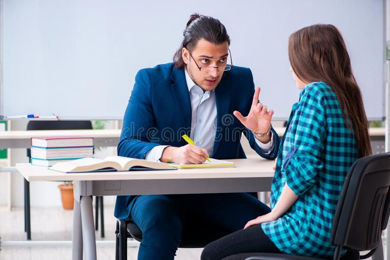 Młody przystojny nauczyciel i żeński uczeń w sali lekcyjnej zdjęcia royalty free