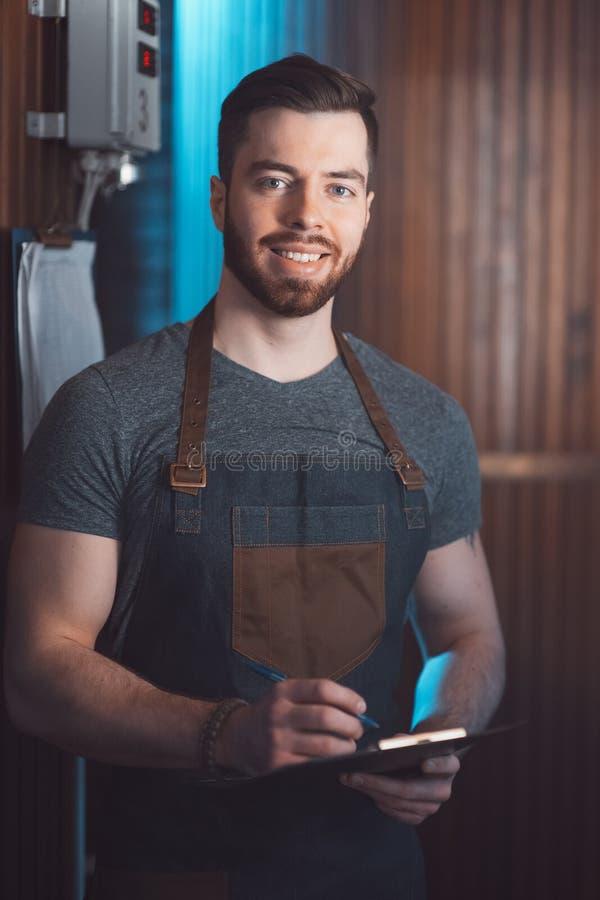 Młody przystojny piwowar w fartuchu z pastylką w jego wręcza a fotografia stock