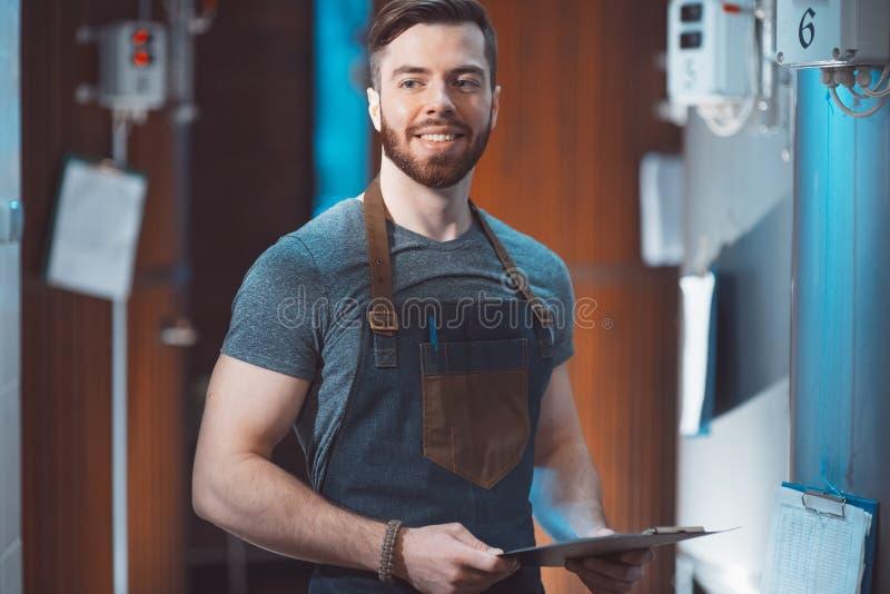 Młody przystojny piwowar w fartuchu z pastylką w jego wręcza a zdjęcie royalty free