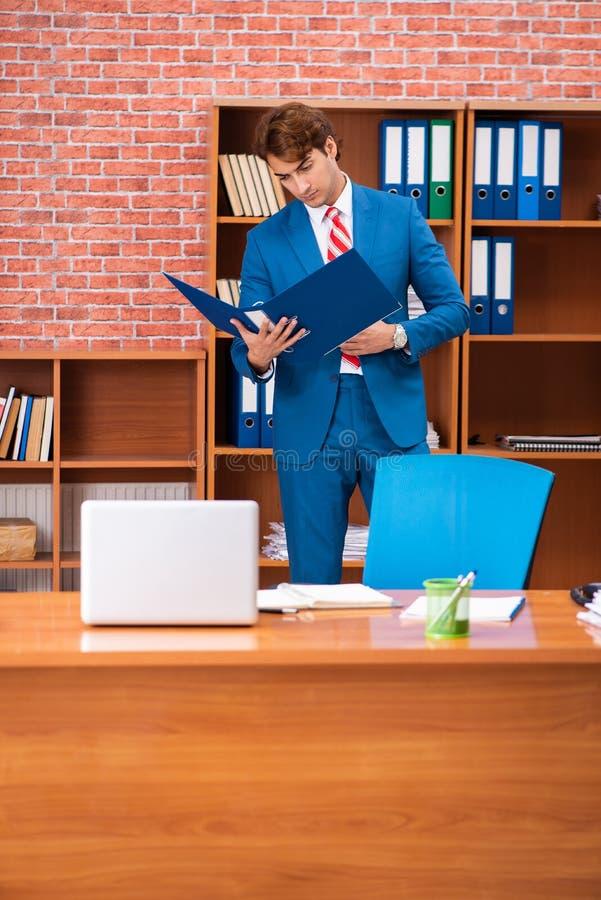 Młody przystojny pracownika obsiadanie w biurze obraz stock
