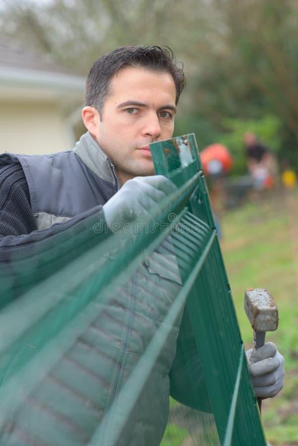 Młody przystojny przedsiębiorca instaluje ogrodzenie w intymnym ogródzie zdjęcia royalty free