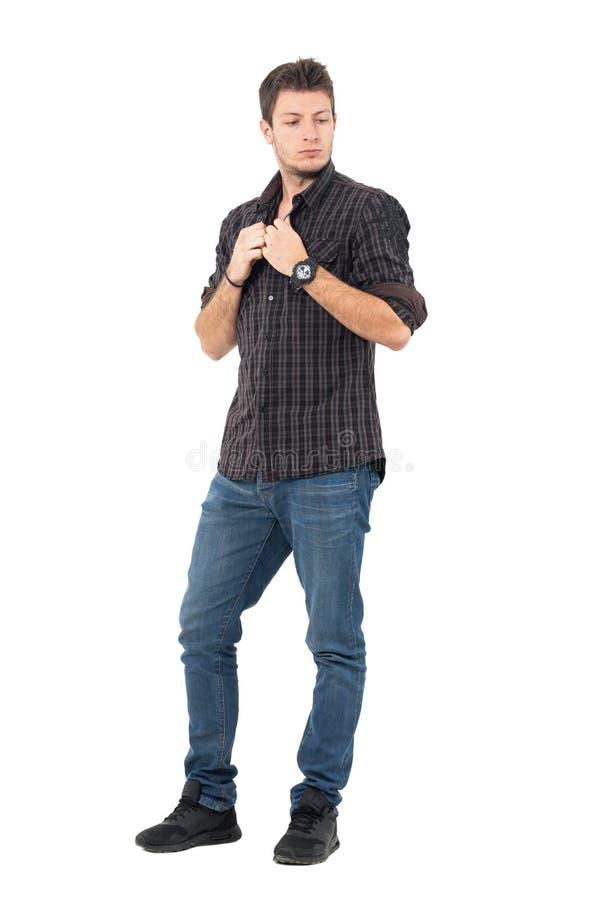 Młody przystojny przypadkowy mężczyzna zapina szkockiej kraty koszula patrzeje w dół zdjęcie royalty free