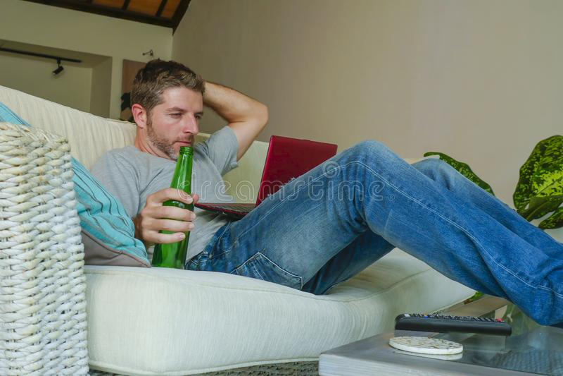 Młody przystojny szczęśliwy mężczyzna siedzi kanapy leżankę pracuje online z laptopem używa netbook w domu relaksował wygodny pić zdjęcie royalty free