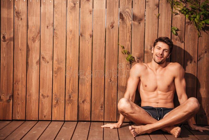 Młody przystojny uśmiechnięty mężczyzna w swimwear obsiadaniu z nogami krzyżować obraz stock