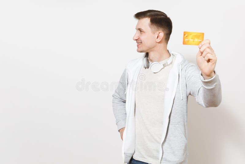Młody przystojny uśmiechnięty mężczyzny uczeń w koszulce, lekka bluza sportowa z hełmofonami wokoło szyi pokazuje pomarańczową ka zdjęcia stock