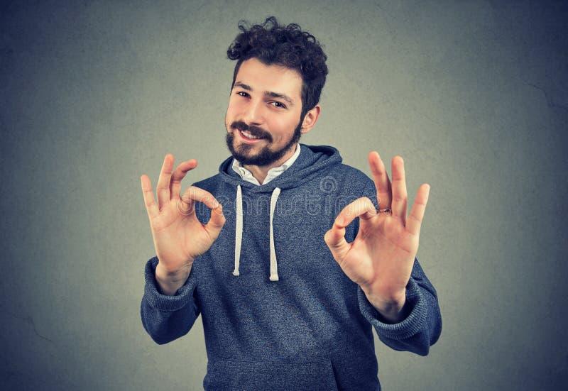 Młody przystojny ufny mężczyzna pokazuje ok znaka zdjęcie stock