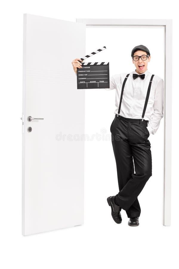 Młody reżyser filmowy opiera na otwarte drzwi obraz royalty free