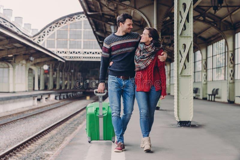 Młody rodzinny para uścisk, spojrzenie przy each inny z uśmiechem, odzież cajgami i ciepłymi pulowerami i, niesiemy walizkę, poza zdjęcia stock