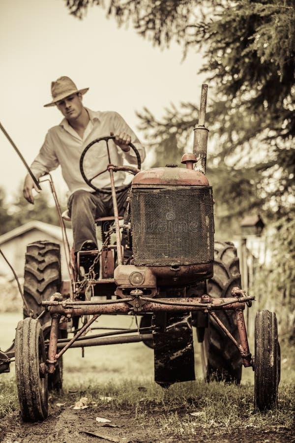 Młody rolnik na rocznika ciągniku zdjęcie royalty free