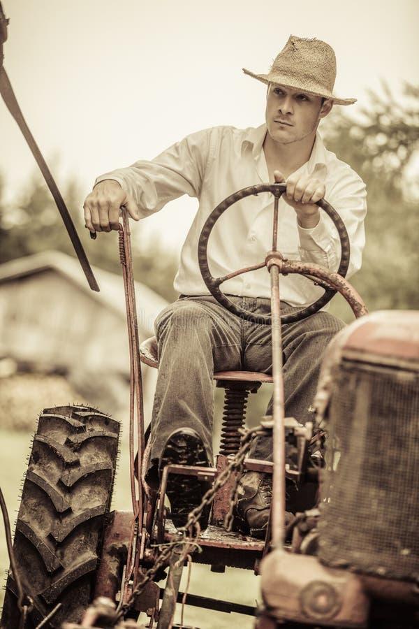 Młody rolnik na rocznika ciągniku zdjęcia royalty free