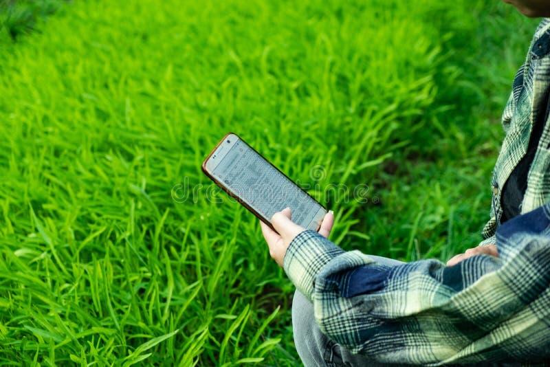Młody rolnik obserwuje niektóre map warzywa segregującego w telefonie komórkowym, Eco organicznie nowożytny mądrze gospodarstwo r obrazy stock