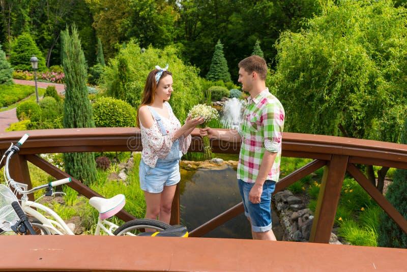 Młody romantyczny mężczyzna daje kwiaty jego dziewczyna w parku zdjęcia royalty free