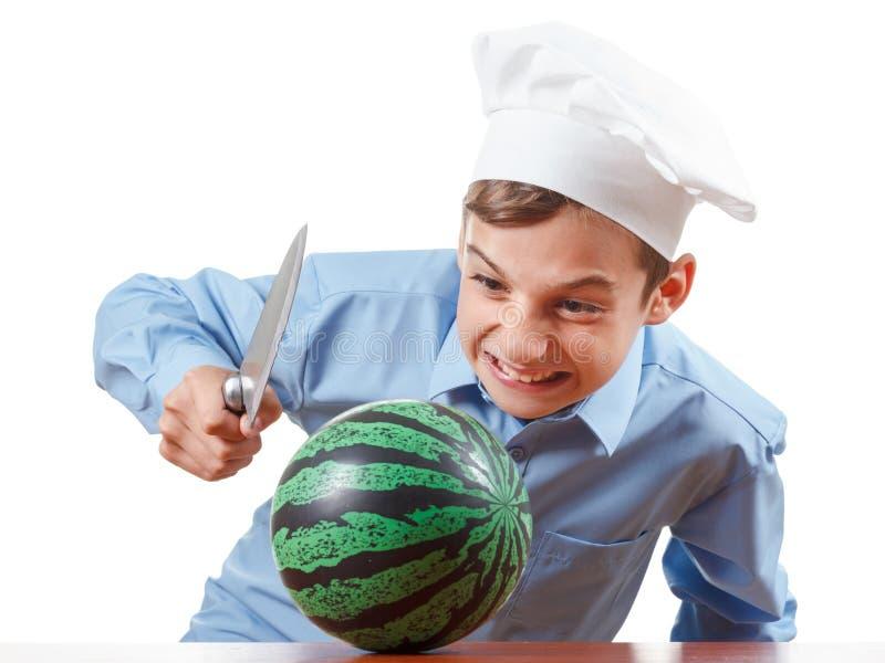 Młody rozochocony nastolatka guffaw, śmia się głośnego i humor w szefa kuchni kapeluszu Odosobniony studio zdjęcie royalty free
