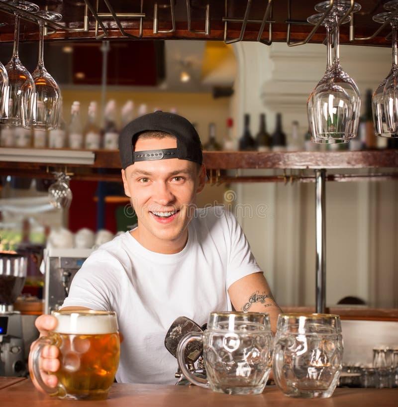 Młody rozochocony szczęśliwy barman ofiary piwo klient obraz stock