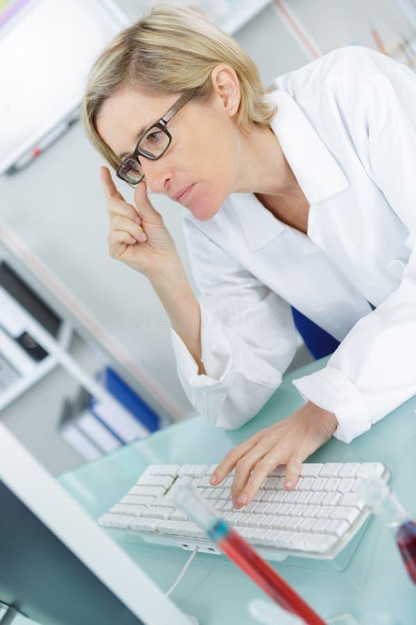Młody rozważny żeński chemik pracuje w lab zdjęcia stock