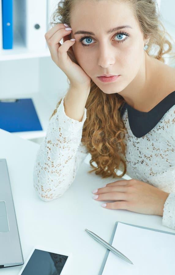 Młody rozważny urzędnik z notatnikiem w biurze, miejsce pracy patrzeje kamerę zdjęcie royalty free