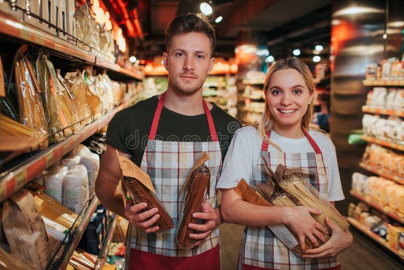 Młody ruchliwie mężczyzna i kobieta trzymamy pakować makaron w rękach w sklepie spożywczym Patrzeją na kamerze i uśmiechu Pozytyw obrazy stock