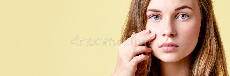 Młody rudzielec nastolatek z jaźnią wydaje patrzeć w lustro Dziewczyna sprawdza jej skórę z niskim jaźń szacunekiem fotografia stock