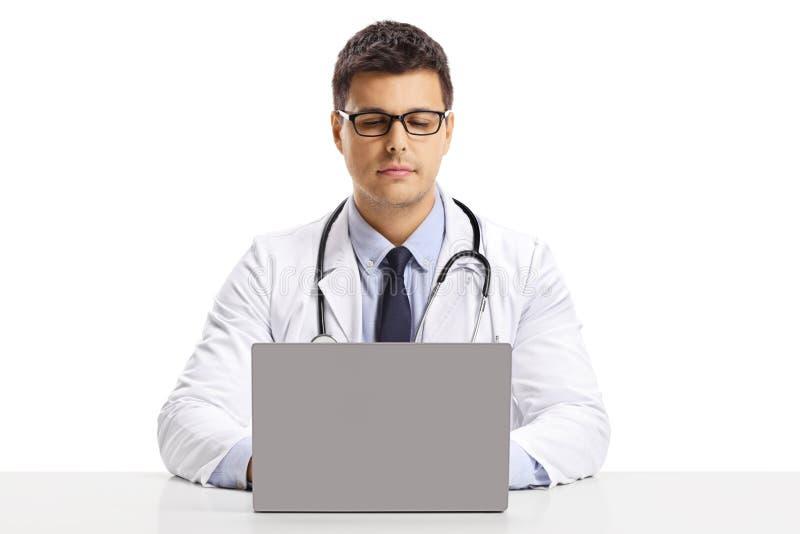 Młody samiec lekarki obsiadanie przy biurkiem i działanie na laptopie fotografia royalty free