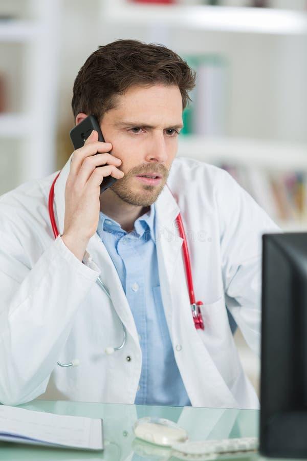 Młody samiec lekarki obsiadanie przy biurkiem i telefonowaniem obrazy stock