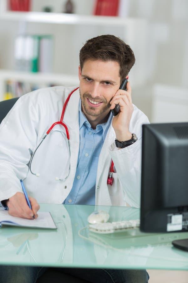 Młody samiec lekarki obsiadanie przy biurkiem i telefonowaniem obraz royalty free