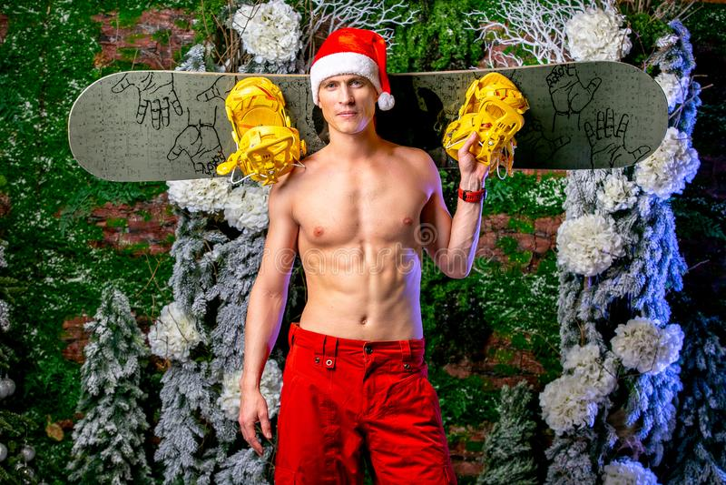 Młody seksowny sporty młody człowiek w czerwieni dyszy i Santa ` s nakrętka utrzymuje snowboard na jego ramionach zdjęcie stock