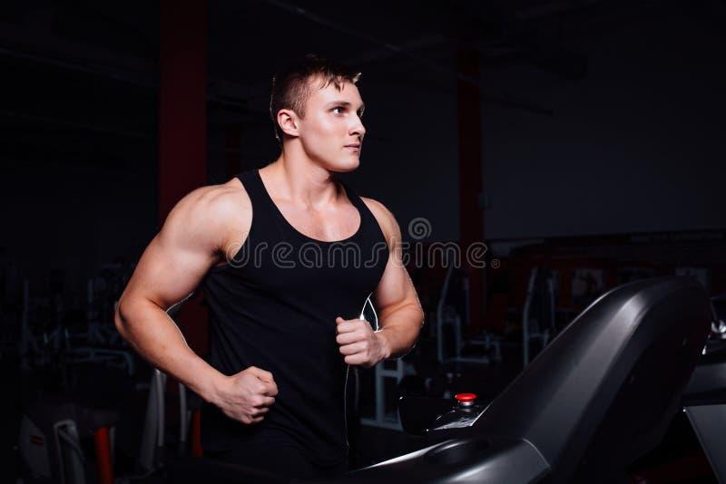 Młody silny duży mężczyzna sprawności fizycznej model w gym bieg na karuzeli z bidonem obraz stock
