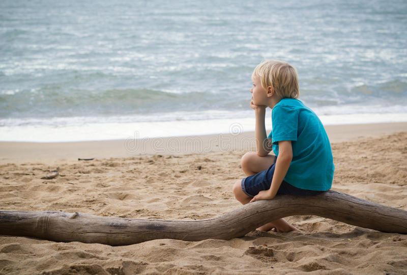 Młody smutny chłopiec główkowanie na plaży zdjęcie royalty free